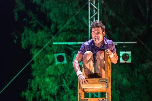 """Frightened Phare Circus performer on a chair tower on the outdoor stage in the show """"Chills"""""""