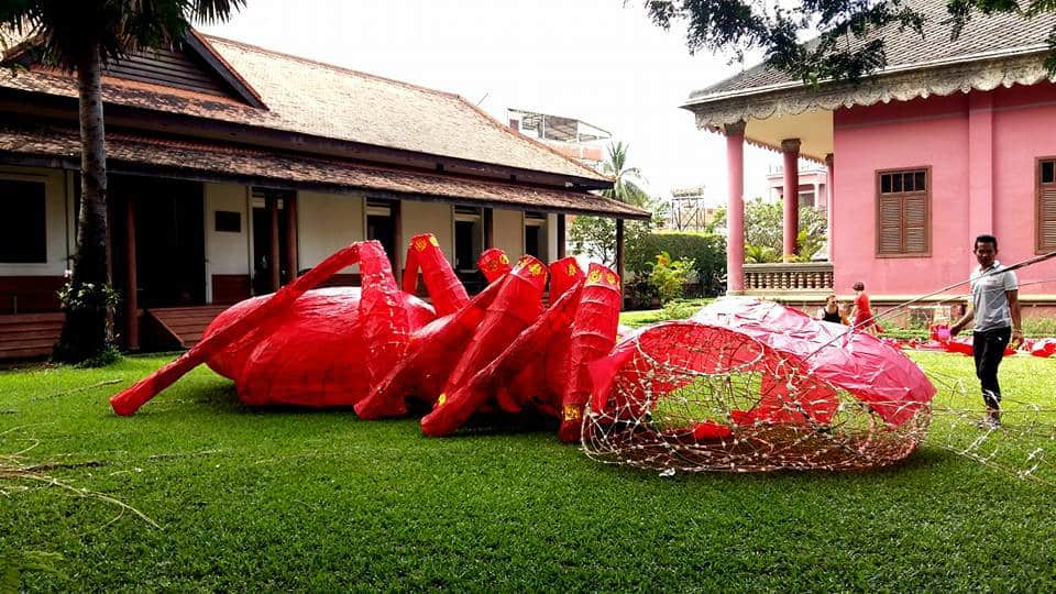 Giant Puppet Parade - large red ant on the grass