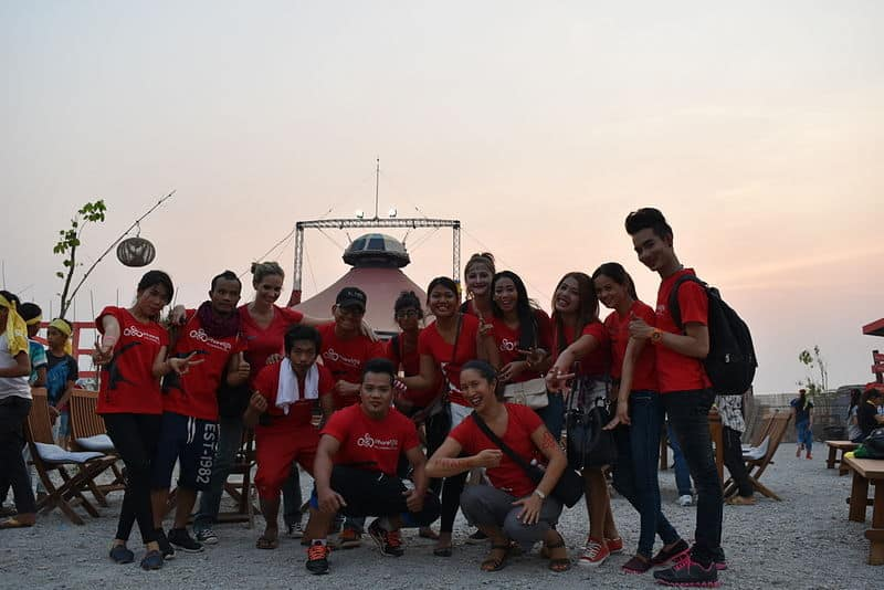 Phare Circus staff and artists in red t-shirts pose for group photo in front of the big top