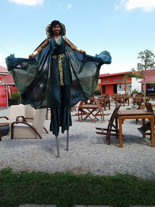 Phare Circus artist on stilts in billowing costume outside iconic red big top