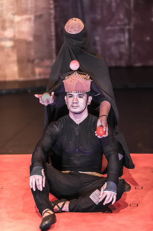 """Phare Circus live show """"Influence"""" - juggler with black robe and coconut mask with seated king"""