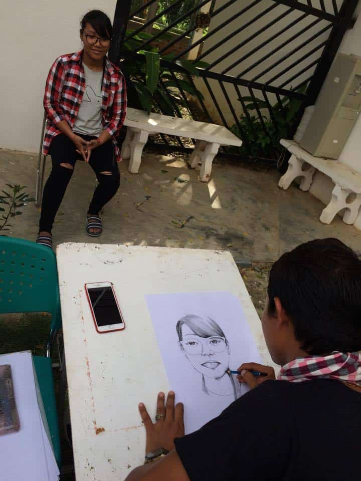 Young woman has portrait sketched by Phare Ponleu Selpak visual artist