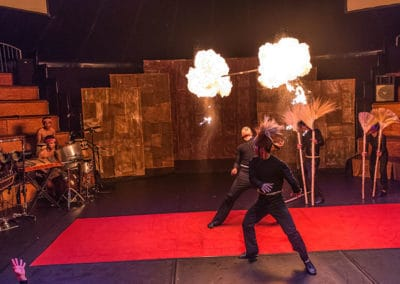 """Phare Circus performance """"Influence"""": artist throws fire baton in the air, watched by musicians and perfomers"""