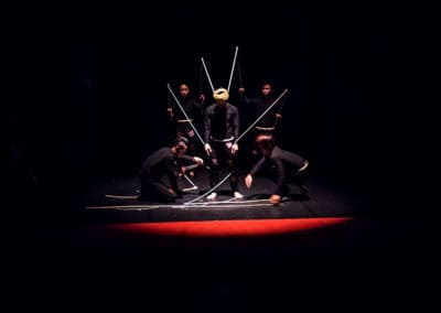 """Phare Circus performance """"Influence"""": performers in black costumes attach strings to a """"puppet"""""""