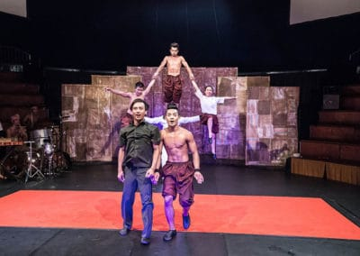 """Phare Circus show """"Influence"""": 2 male performers stand in front of human pyramid, having just jumped through"""