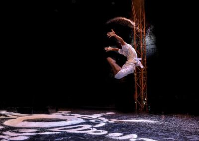 """Phare Circus show - """"White Gold"""" - man celebratory leap in the air over Buddhist mandala designed with rice"""