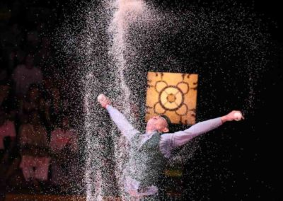 """Phare Circus performance """"White Gold""""- male artist juggling under shower of rice"""